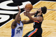 San Antonio Spurs guard Derrick White, right, takes a shot over Orlando Magic center Wendell Carter Jr. (34) during the first half of an NBA basketball game, Monday, April 12, 2021, in Orlando, Fla. (AP Photo/John Raoux)