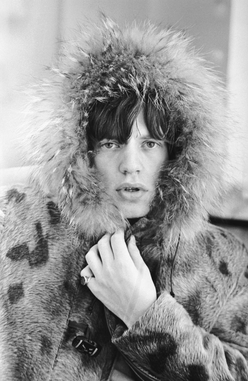 <p>Mick Jagger posing in a fur parka, with a fur trimmed hood, 1964.</p>