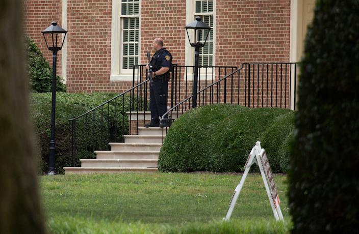 A police officer stands out in front of City Hall next to the building where eleven people were killed during a mass shooting at the Virginia Beach city public works building, May 31, 2019 in Virginia Beach, Va.  (Photo: L. Todd Spencer/The Virginian-Pilot via AP)