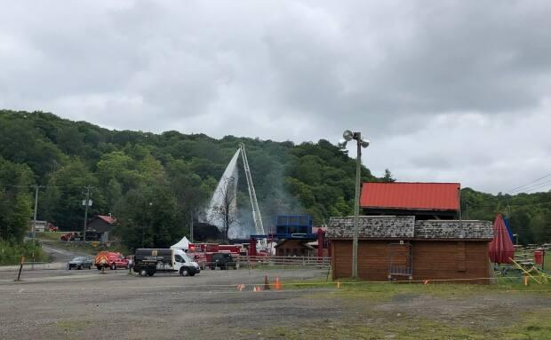 Crews douse the main chalet at the Mont Cascades resort near Cantley, Que., with water following a fire on Aug. 1, 2021.  (Rosalie Sinclair/Radio-Canada - image credit)