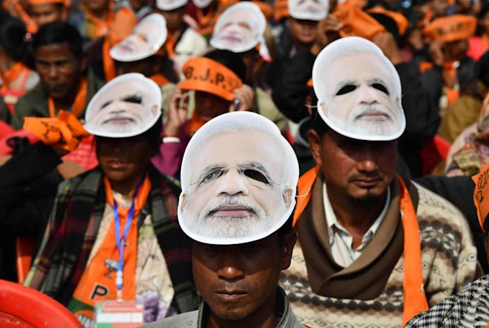 Supporters of the Bharatiya Janata Party (BJP), wearing masks of Indian Prime Minister Narendra Modi, listen to Modi during a public rally in Shillong on December 16, 2017.