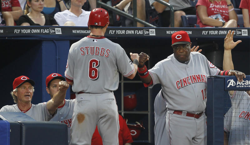 Cincinnati Reds' Drew Stubbs (6) is greeted by manager Dusty Baker, right, and bench coach Chris Speier (35) after scoring in the fourth inning of a  baseball game against the Atlanta Braves, Saturday, May 28, 2011, in Atlanta. Stubbs reached a three-run double and scored on a Reds second baseman Brandon Phillips double. (AP Photo/John Bazemore)