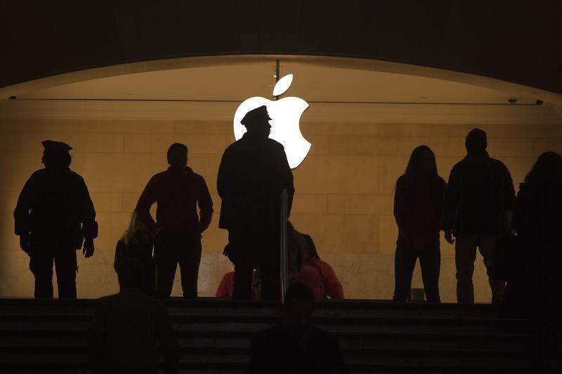 A police officer is silhouetted against the Apple logo in Grand Central Terminal in New York