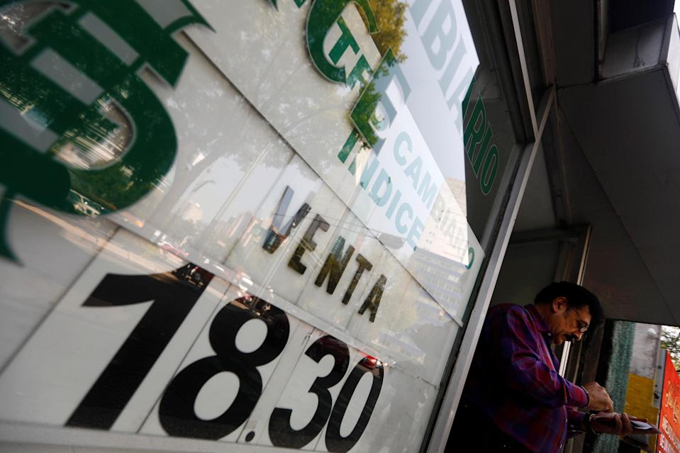 A man is pictured next to a board displaying the exchange rate for Mexican peso and U.S. dollar at a foreign exchange house in Mexico City, Mexico, October 20, 2017. REUTERS/Edgard Garrido