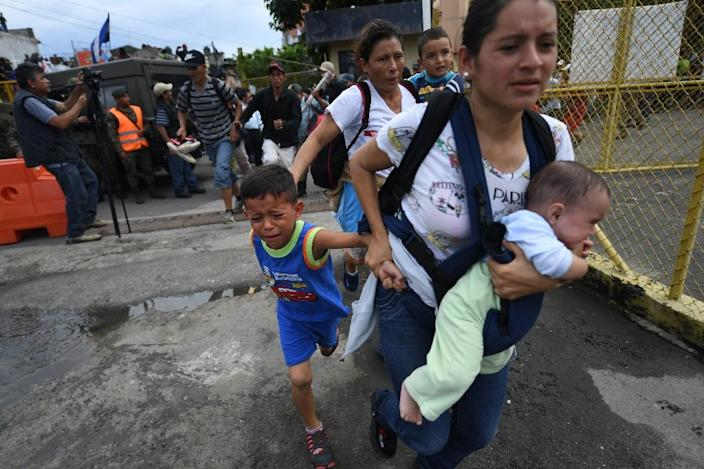Women holding crying children by the hand or pressing their infants to their chests streamed past the broken metal barriers and onto the bridge into Mexico (AFP Photo/Pedro Pardo )