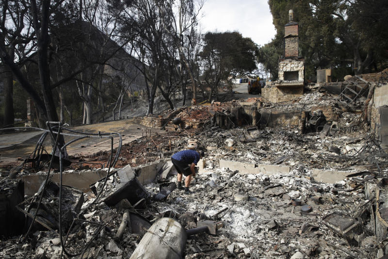FILE - In this Nov. 13, 2018 file photo Roger Kelton searches through the remains of his mother-in-law's home leveled by the Woolsey Fire, in the southern California city of Agoura Hills. A Southern California utility has agreed to pay $360 million to settle lawsuits brought by cities, counties and other public agencies over deadly wildfires sparked by its equipment in the last two years, including one that was later blamed for a mudslide that killed more than 20 people. An attorney for 23 public entities said Wednesday, Nov. 13, 2019, that Southern California Edison has agreed to the sum to repay taxpayers for firefighting and damage from the Thomas Fire in 2017 and Woolsey Fire last year. (AP Photo/Jae C. Hong,File)
