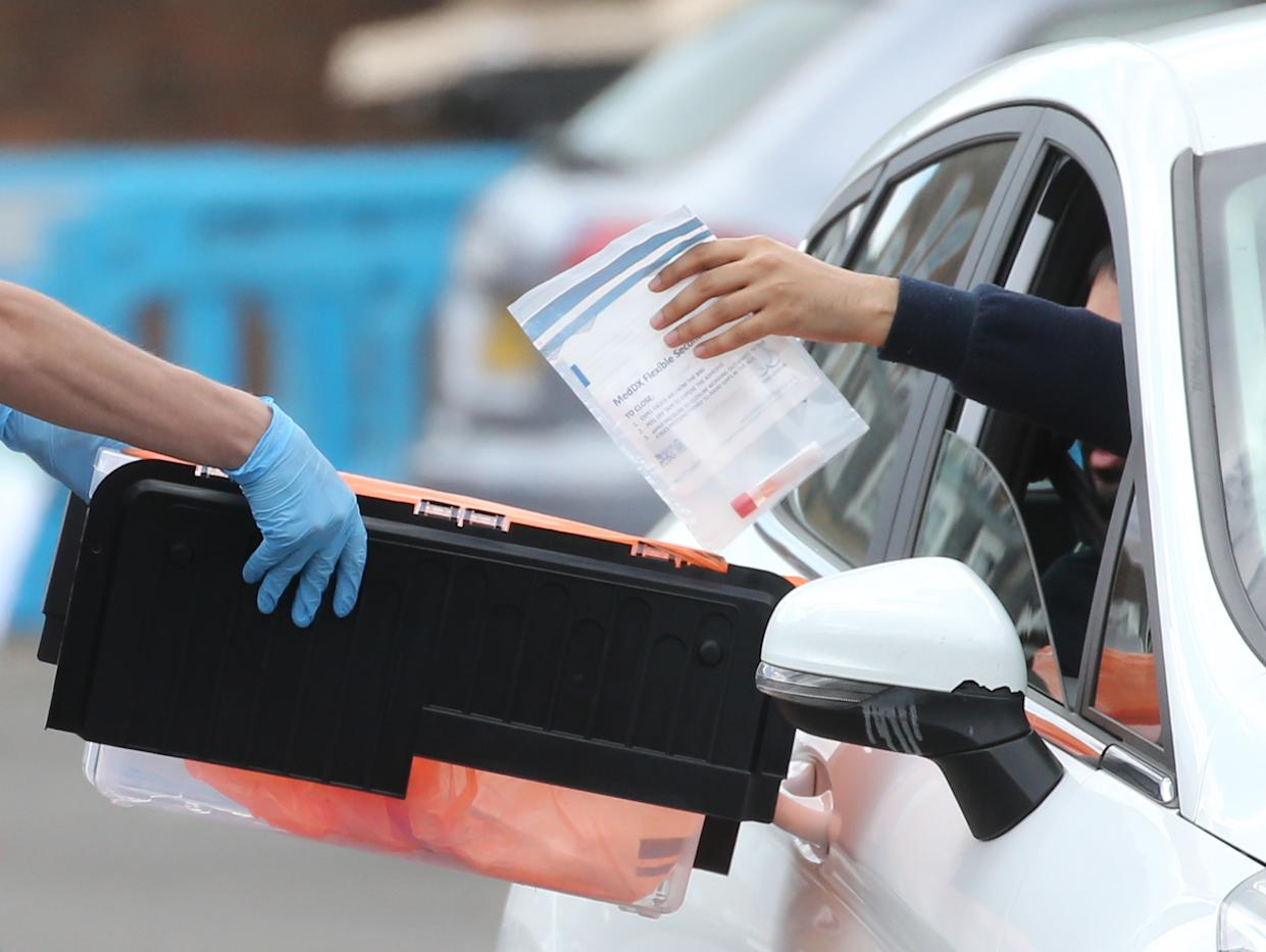 A driver hands in a swab test to soldiers helping at a pop-up covid19 drive-through testing centre in Dalston, Hackney, east London, as the UK continues in lockdown to help curb the spread of the coronavirus. Picture date: Saturday May 2, 2020.