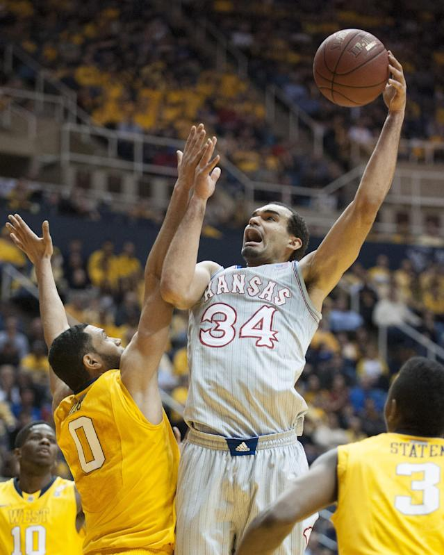 Kansas' Perry Ellis, right, shoots over West Virginia's Remi Dibo during the first half of an NCAA college basketball game Saturday, March 8, 2014, in Morgantown, W.Va. (AP Photo/Andrew Ferguson)