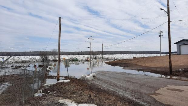 A road in Fort Simpson flooded with water. Residents were told to evacuate over the weekend because of the extremely high water levels coming into the village. Norman Wells Mayor Frank Pope said they have room for at least 100 people if communities needed to be evacuated. (Sarah Camsell - image credit)