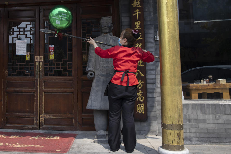 A waitress wearing a mask to curb the spread of the coronavirus uses the pike of a terra-cotta warrior sculpture to remove a balloon as she spreads to open a restaurant for business in Beijing on Wednesday, July 8, 2020. (AP Photo/Ng Han Guan)