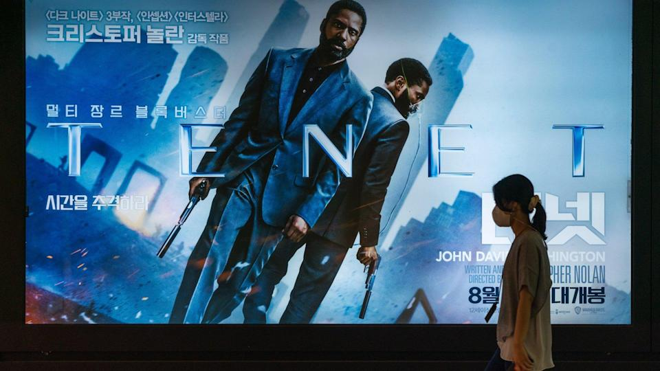 Mandatory Credit: Photo by Simon Shin/SOPA Images/Shutterstock (10757557a)A woman wearing protective mask walks by a billboard of the movie 'TENET'.