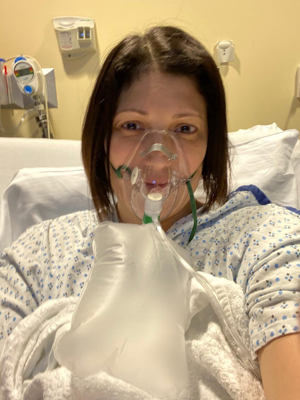 Sofia Burke, 43, of Elmwood Park, uses a non-rebreather mask to deliver high concentrations of oxygen while hospitalized with COVID on Nov. 25, 2020.