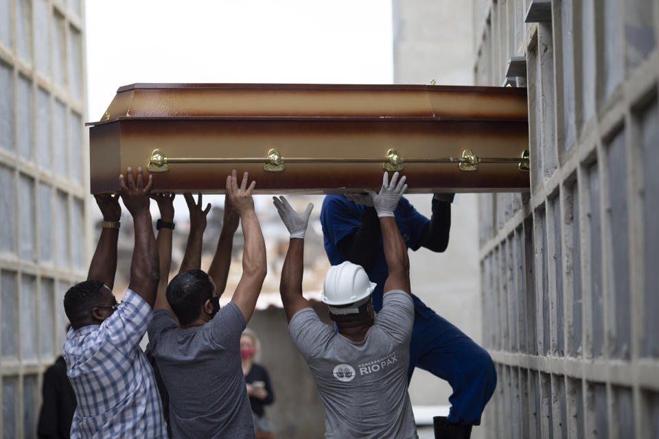 The remains of a woman who died from complications related to COVID-19 are placed into a niche by cemetery workers and relatives at the Inahuma cemetery in Rio de Janeiro, Brazil, Tuesday, April 13, 2021. (AP Photo/Silvia Izquierdo)
