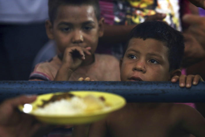 <p>Venezuelan children wait for a free meal at a migrant shelter set up at the Tancredo Neves Gymnasium in Boa Vista, Roraima state, Brazil on March 8, 2018. This is the largest of three shelters for migrants in the city, and has 700 people despite being equipped for 200. (Photo: Eraldo Peres/AP) </p>