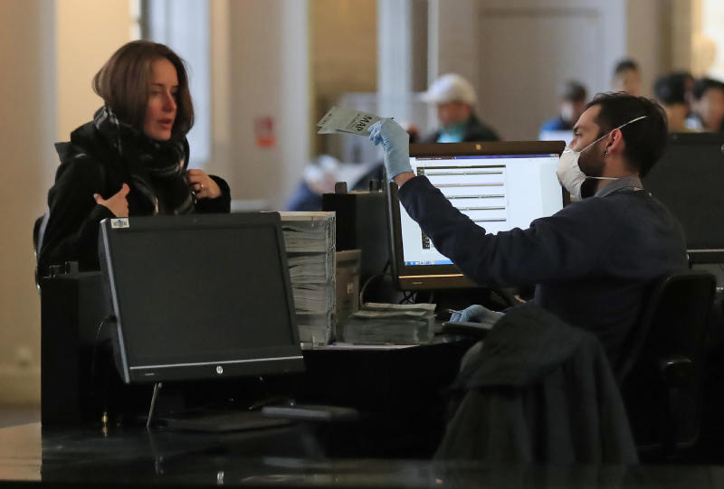 An employee of the Palace of Versailles wearing a mask and gloves sells tickets to a tourist at the castel in Versailles, west of Paris, Thursday, March 5, 2020. The palace has distributed masks, gloves and disinfectant gels to employees and held talks with their union representatives after staffers at the Louvre, another major tourist draw, walked off the job for two days for fear of contamination of the COVID-19. (AP Photo/Michel Euler)