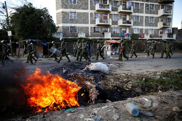 <p>Kenyan police walk past burning tires set on fire during clashes between supporters of Kenyan opposition National Super Alliance (NASA) and police in Nairobi, Kenya, Nov. 28, 2017. (Photo: Baz Ratner/Reuters) </p>