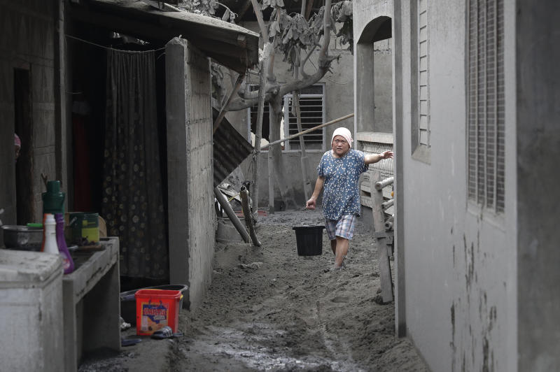 In this Jan. 14, 2020, photo, a resident fetches water at their volcanic ash covered village in Laurel, Batangas province, southern Philippines, as Taal volcano continues to spew ash. So far no one has been reported killed in the eruption, but the disaster is spotlighting the longstanding dilemma of how the government can move settlements away from danger zones threatened by volcanoes, landslides, floods and typhoons in one of the world's most disaster-prone countries. (AP Photo/Aaron Favila)