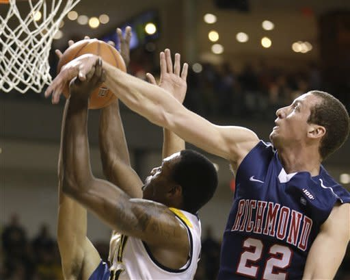 Richmond forward Greg Robbins (22) blocks a shot by Virginia Commonwealth guard Treveon Graham, left, during the first half of an NCAA college basketball game in Richmond, Va., Wednesday, March 6, 2013. (AP Photo/Steve Helber)