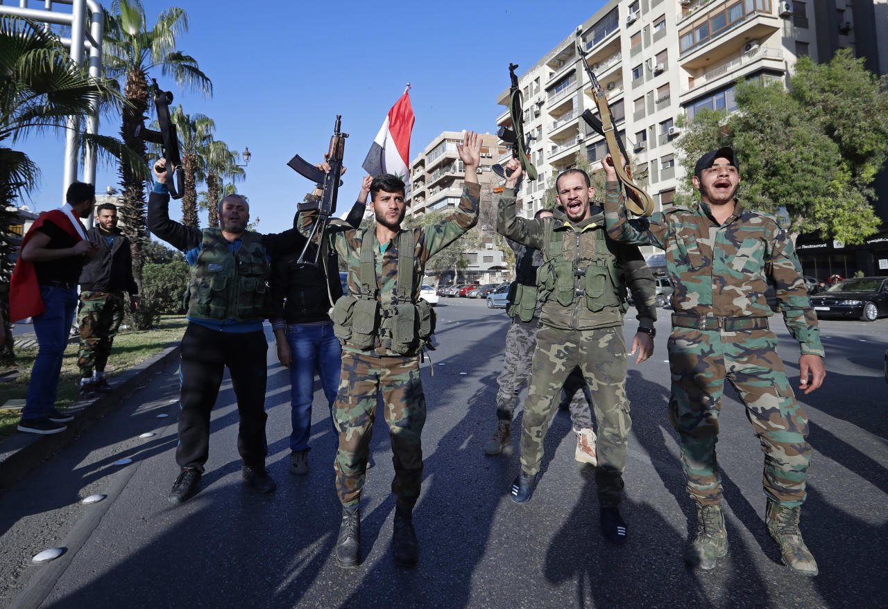 <p>Syrian soldiers hold their weapons as they dance and chant slogans against U.S. President Trump during demonstrations following a wave of U.S., British and French military strikes to punish President Bashar Assad for suspected chemical attack against civilians, in Damascus, Syria, Saturday, April 14, 2018. (Photo: Hassan Ammar/AP) </p>