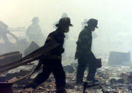 <p>A group of firefighters search the rubble near the base of the destroyed World Trade Center. (Reuters)</p>