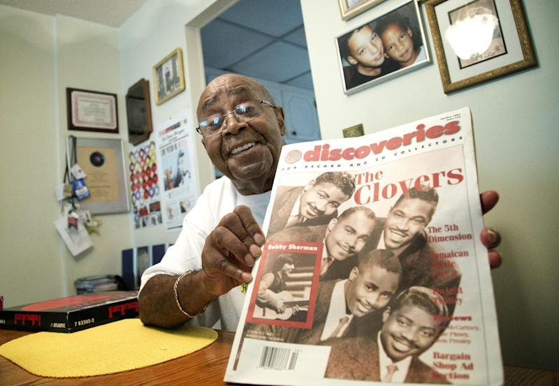 """Harold Winley, who performed """"Love Potion No. 9"""" and other hits with the band The Clovers in the 50s, poses for photos Friday, Aug. 2, 2013 in Lauderdale Lakes, Fla. home, as he holds an old trade publication. The Clovers were featured on the cover. The 80-year-old says a splinter group is trying to keep him from performing using the band's name. (AP Photo/J Pat Carter)"""