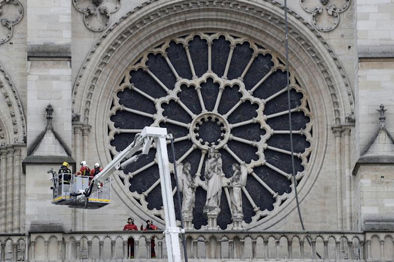 Firefighters outside the south transept Rose window. Experts say it could take decades to restore Notre-Dame Cathedral (AFP Photo/Thomas SAMSON)