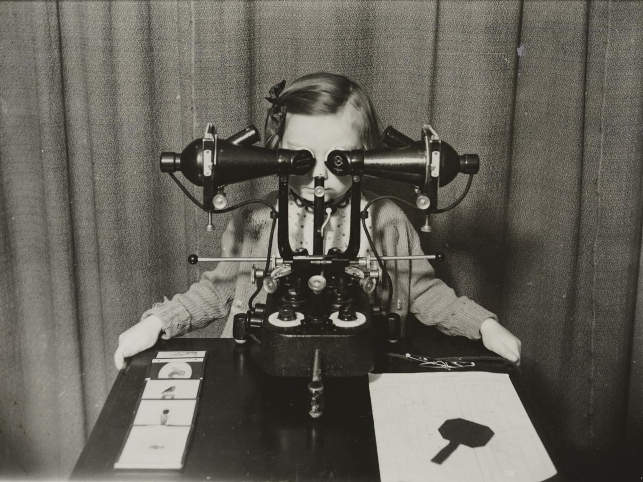 <p>'Treatment of squint. Picture shows a child sitting at the synoptoscope – an instrument for restoring binocular vision.' (Historic England) </p>