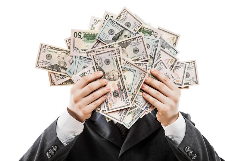 Businessman holding money in front of his face