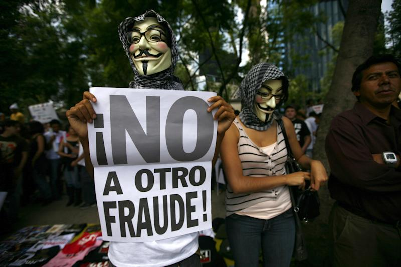 """Wearng a Guy Fawkes mask, a Mexican unhappy with the presidential election results, holds a banner that reads in Spanish; """"No to another fraud!,"""" during a march in Mexico City, Saturday, July 7, 2012. The protestors are marching in rejection of the final count in the presidential election showing former ruling party candidate Enrique Pena Nieto as the victor. They believe the PRI engaged in vote-buying that illegally tilted millions of votes. PRI officials deny the charge. (AP Photo/Marco Ugarte)"""