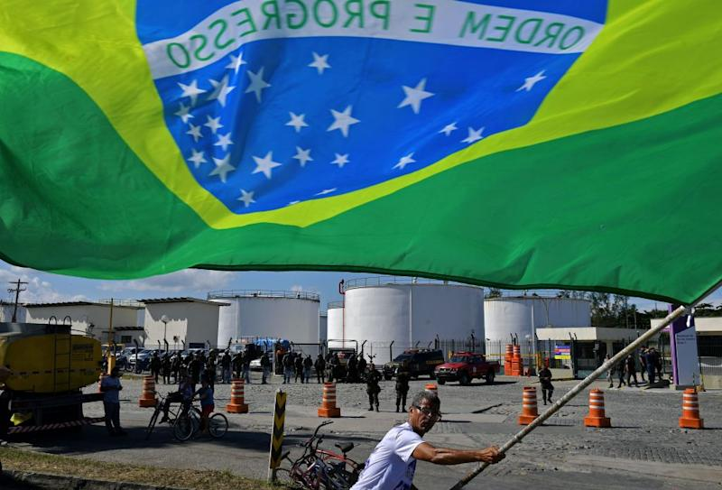 TOPSHOT - A protestor waves the Brazilian national flag outside the Duque de Caxias refinery in metroplitan Rio de Janeiro, Brazil, on May 28, 2018, where soldiers have been deployed to guarantee the safe transport of fuel for essential services. - A truckers' strike paralyzing fuel and food deliveries across Brazil entered an eighth day Monday but with hopes of relief after unpopular President Michel Temer caved in to the strikers' key demand. Road blockages by truckers remained in place across 21 of the country's 27 states, G1 news site reported. (Photo by Carl DE SOUZA / AFP) (Photo credit should read CARL DE SOUZA/AFP via Getty Images)