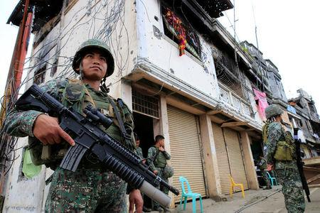 FILE PHOTO: Government soldiers stand guard in front of damaged building and houses in Sultan Omar Dianalan boulevard at Mapandi district in Marawi city, southern Philippines September 13, 2017. REUTERS/Romeo Ranoco