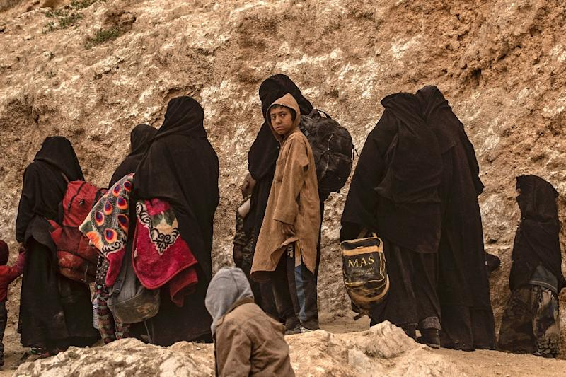 Suspected wives and children of Islamic State group fighters exit the village of Baghouz in the eastern Syrian province of Deir Ezzor (AFP Photo/Delil souleiman)