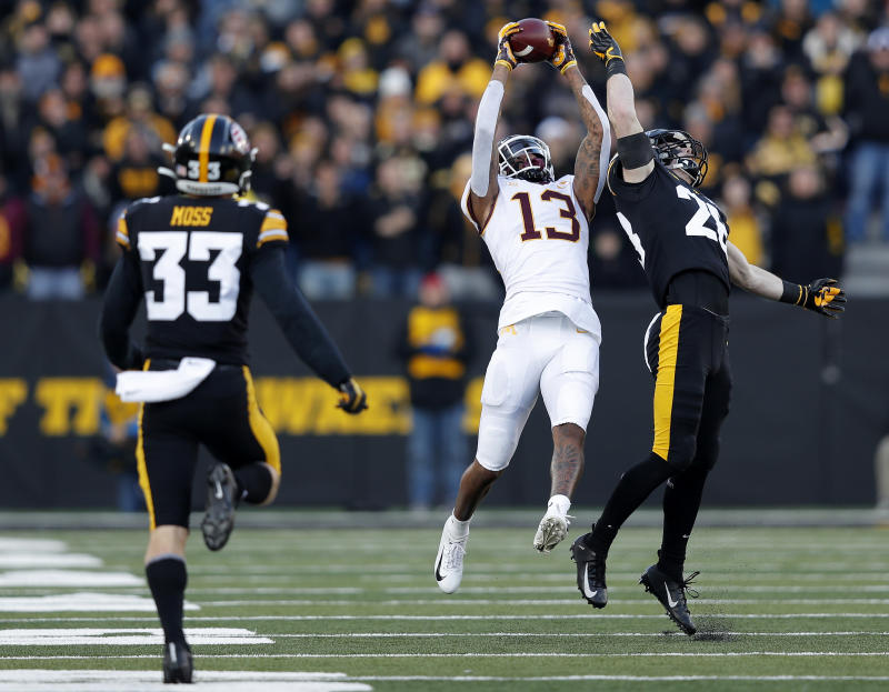 Minnesota wide receiver Rashod Bateman, center, pulls down a reception over Iowa defensive back Jack Koerner, right, during the first half of an NCAA college football game, Saturday, Nov. 16, 2019, in Iowa City, Iowa. (AP Photo/Matthew Putney)