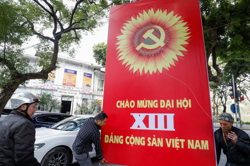 Workers set up a poster for upcoming 13th National Congress of the ruling Communist Party of Vietnam, on a street in Hanoi