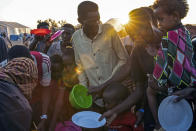 Refugees who fled the conflict in Ethiopia's Tigray region wait to get cooked rice served by Sudanese local volunteers at Um Rakuba refugee camp in Qadarif, eastern Sudan, Monday, Nov. 23, 2020. (AP Photo/Nariman El-Mofty)