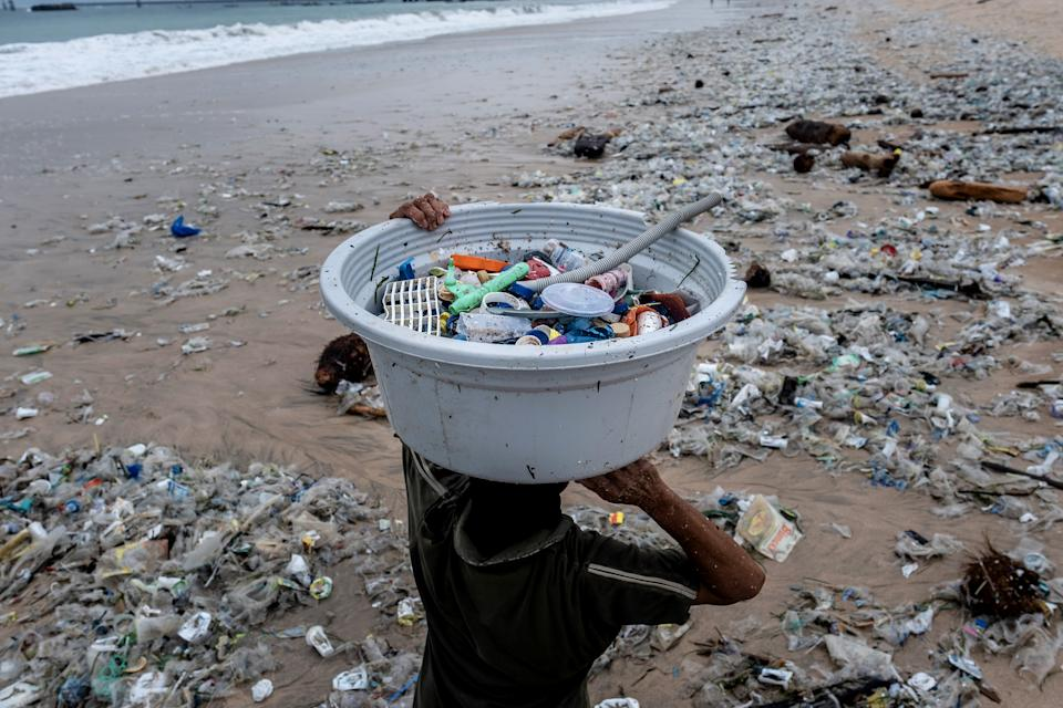 BALI, INDONESIA - JANUARY 30 : Saarinah (45) carries recyclable plastic trash on January 30, 2021 in Kedonganan, Bali, Indonesia. During the northwest monsoon season, she works to collect the recyclable plastic trash which brought in by the strong waves. She can collect 8kg per day and earns Rp.4000 per kg. In Bali, famed among tourists for its beaches and sunsets, the northwest monsoon brings a different kind of arrival - vast amounts of plastic waste. From December to March, so much trash washes up on the beaches that the local government struggles to keep up and clean up. Locals and workers have together been collecting 80 tonnes of waste a day as it washes ashore at world-famous beaches from Seminyak to Kuta, the local government said. Almost 75 percent of it is plastic, according to a study by the Center of Remote Sensing and Ocean Sciences at Bali's Udayana University. In the absence of tourism due to Covid-19, the trash problem has become obvious on beaches almost entirely devoid of visitors. Indonesia is part of the U.N.'s Clean Seas campaign, which aims to halt the tide of plastic trash polluting the oceans. As part of its commitment, the government has vowed to reduce marine plastic waste by 70 percent by 2025. (Photo by Agung Parameswara/Getty Images)