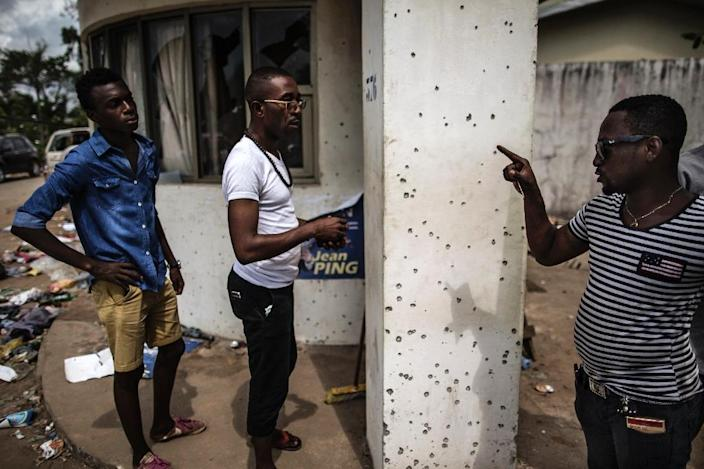 A man points out bullet holes at Gabon's opposition leader Jean Ping's headquarters on September 3, 2016 in Libreville (AFP Photo/Marco Longari)
