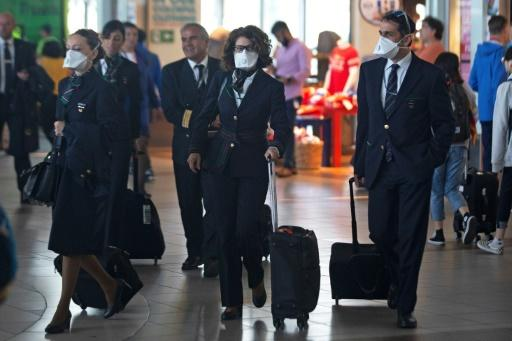 Airline staff wear protective masks at Santiago's  international airport on March 14, 2020