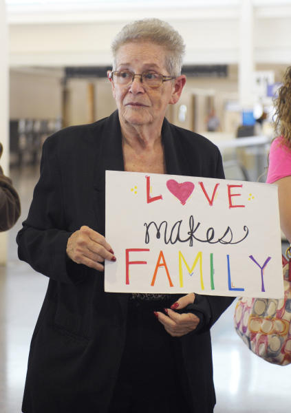 """Carolyn Wiley of Tulsa holds a """"Love Makes Family"""" sign as Oklahomans for Equality gathered at Tulsa International Airport with their signs for a send off celebration in support for the plaintiffs in the Oklahoma Marriage Equality lawsuit as they head to the 10th Circuit Court of Appeals in Denver, Wednesday, April 16, 2014. (AP Photo/Brandi Simons)"""