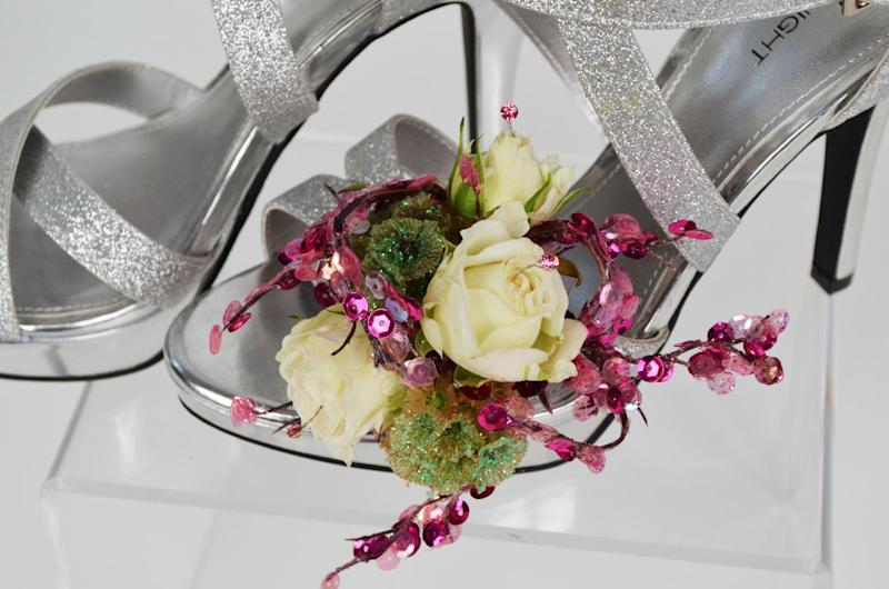 This product image released by Gillespie Florists, Inc. shows a floral decoration for prom shoes. The decoration is made of three white tea roses, three glittered scabiosa pods, pink sequin accents and pink rhinestones. (AP Photo/Gillespie Florists, Inc.)