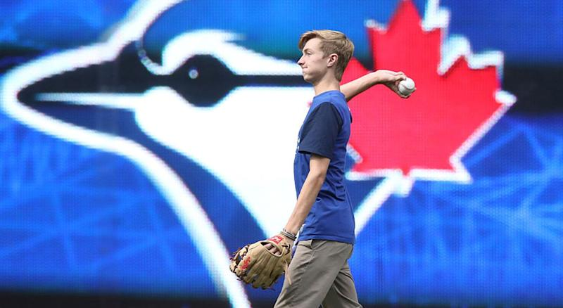 TORONTO, CANADA - AUGUST 14: Braden Halladay the son of former player Roy Halladay #32 of the Toronto Blue Jays plays catch in the outfield after the game before which his father was honored at the fortieth season celebrations before the start of MLB game action against the Houston Astros on August 14, 2016 at Rogers Centre in Toronto, Ontario, Canada. (Photo by Tom Szczerbowski/Getty Images)