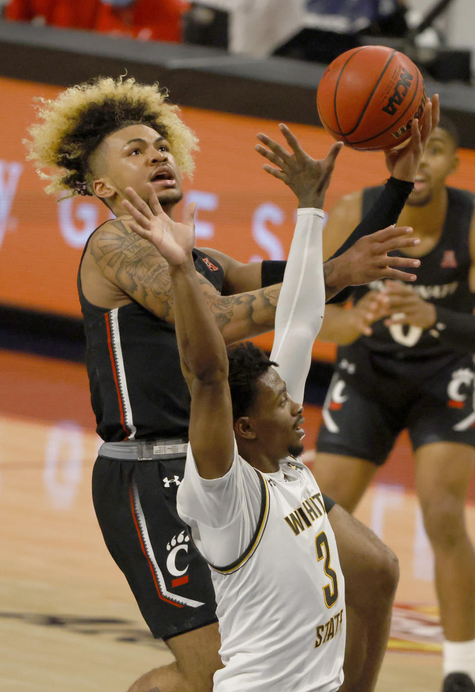 Cincinnati guard Mike Saunders (3) goes up for a shot as Wichita State guard Alterique Gilbert (3) defends during the first half of an NCAA college basketball game in the semifinal round of the American Athletic Conference men's tournament Saturday, March 13, 2021, in Fort Worth, Texas. (AP Photo/Ron Jenkins)