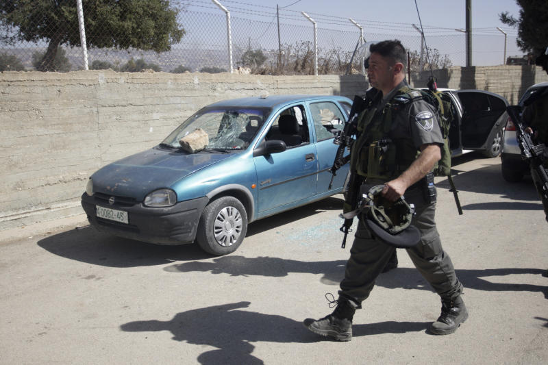 An Israeli policeman walks by a damaged car inside a schoolyard in the West Bank village of Jaloud, near Nablus, Wednesday, Oct .9, 2013. Residents of the village said that masked Jewish settlers burst into the school, vandalized cars and torched olive trees during a rampage that forced schoolchildren to remain locked in classrooms to keep safe. (AP Photo/Nasser Ishtayeh)