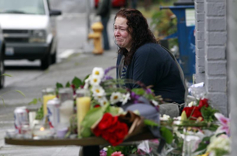 Stacy Davis cries as she sits near a growing memorial at the scene of where a gunman killed four people and severely wounded another in a cafe a day earlier, Thursday, May 31, 2012, in Seattle. Police say he later killed a woman during a carjacking before shooting himself. As officers closed in during a widespread manhunt on Wednesday, the suspect put a gun to his head and pulled the trigger and later died at a hospital. (AP Photo/Elaine Thompson)