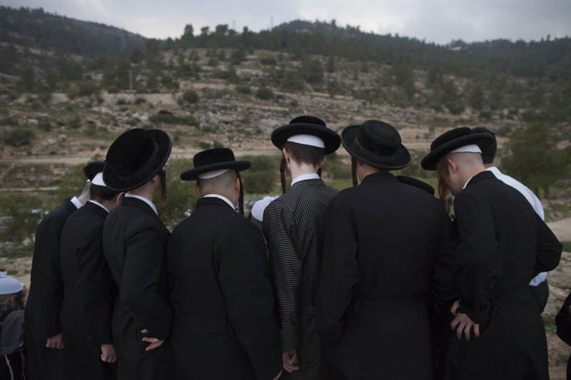 Ultra-Orthodox Jews collect water to make matza during the Maim Shelanoo ceremony at a mountain spring, near Jerusalem, Sunday, April 13, 2014. The water is used to prepare the traditional unleavened bread for the high holiday of Passover which begins Monday.(AP Photo/Dan Balilty)