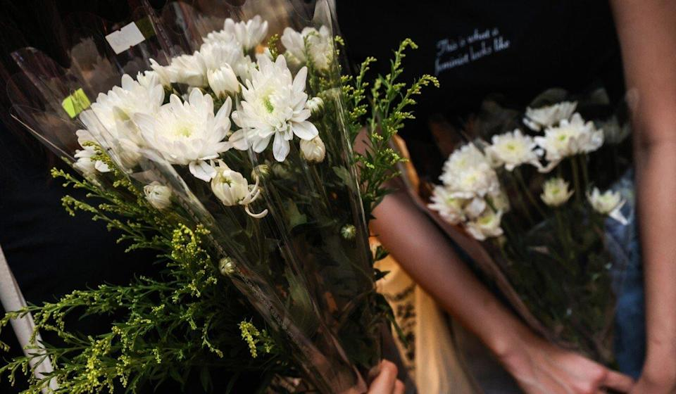 Flowers held by some passers-by in Causeway Bay on Friday night. Photo: K. Y. Cheng
