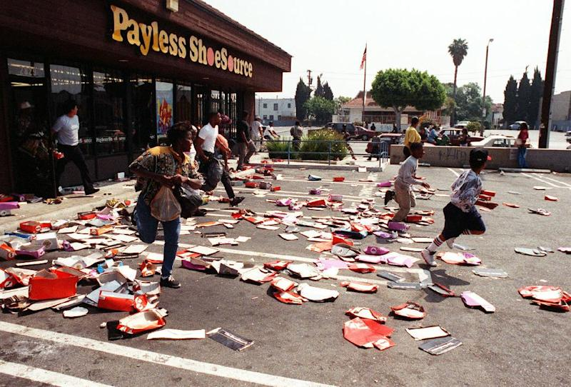 FILE - This April 30, 1992 file photo shows looters running with stolen merchandise from a Payless Shoestore near the Crenshaw and Jefferson area of Los Angeles. Rodney King, the black motorist whose 1991 videotaped beating by Los Angeles police officers was the touchstone for one of the most destructive race riots in the nation's history, has died, his publicist said Sunday, June 17, 2012. He was 47. (AP Photo/Akili-Casundria Ramsess, file)