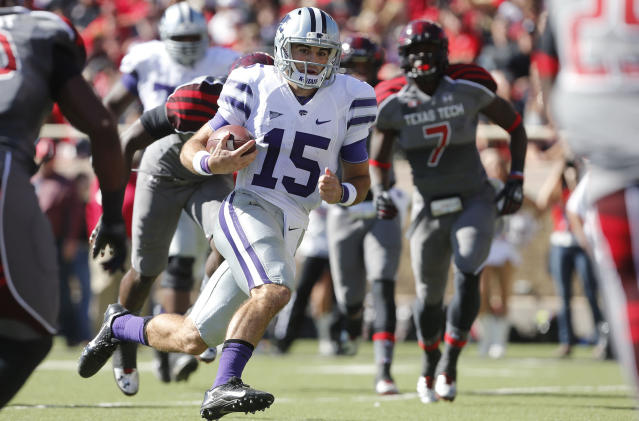 Kansas State's Jake Waters(15) looks for space as he scores a touchdown past Texas Tech's Will Smith (7) during the first half of an NCAA college football game in Lubbock, Texas, Saturday, Nov. 9, 2013. (AP Photo/Lubbock Avalanche-Journal,Stephen Spillman)