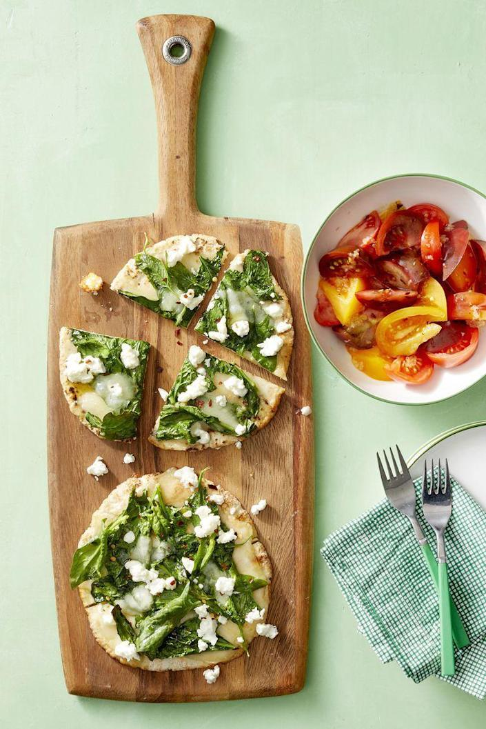 """<p>To satisfy any pizza cravings while still getting in some veggies, try this crispy pita pizza and tomato salad.</p><p><em><a href=""""https://www.womansday.com/food-recipes/food-drinks/a22689014/spinach-and-cheese-pita-pizzas-with-tomato-salad-recipe/"""" rel=""""nofollow noopener"""" target=""""_blank"""" data-ylk=""""slk:Get the Spinach and Cheese Pita Pizzas with Tomato Salad recipe."""" class=""""link rapid-noclick-resp"""">Get the Spinach and Cheese Pita Pizzas with Tomato Salad recipe.</a></em></p><p><strong>Related: </strong><a href=""""https://www.womansday.com/food-recipes/food-drinks/g24/10-pizza-recipes-pizzazz-62794/"""" rel=""""nofollow noopener"""" target=""""_blank"""" data-ylk=""""slk:45 Mouthwatering Recipes for the Best Homemade Pizza"""" class=""""link rapid-noclick-resp"""">45 Mouthwatering Recipes for the Best Homemade Pizza</a></p>"""