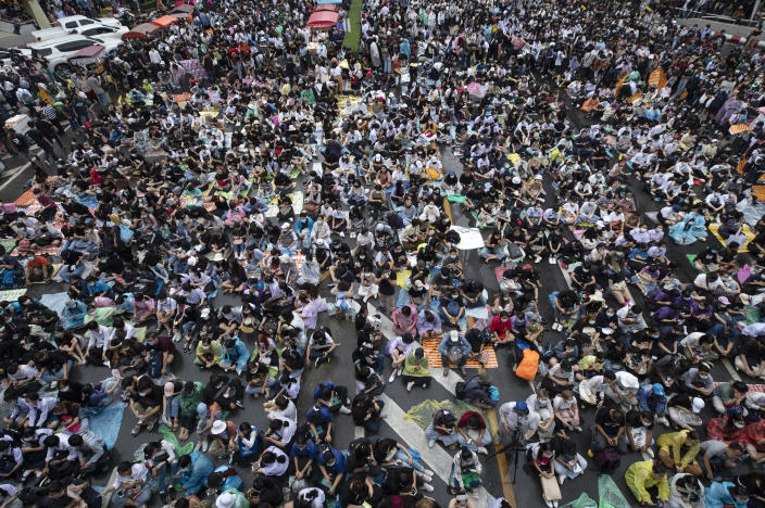 Hundreds of pro-democracy protesters gather in a business district in Bangkok, Thailand, Friday, Oct. 16, 2020. Thailand's prime minister has rejected calls for his resignation as his government steps up efforts to stop student-led protesters from rallying in the capital for a second day in defiance of a strict state of emergency. (AP Photo/Sakchai Lalit)